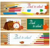 L'orizzontale di nuovo alle insegne di scuola con gli strumenti della scuola e le foglie di autunno su legno sorgono Fotografie Stock