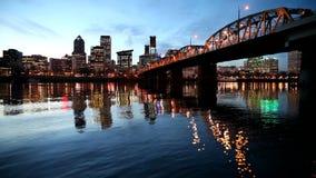 L'orizzonte del centro della città di Portland Oregon lungo il fiume di Willamette con Hawthorne Bridge e l'ora blu innaffiano le stock footage