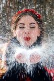 L'orlo della ragazza in rosso soffia la neve dalla palma fotografie stock libere da diritti