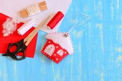 L'ornamento della casa sull'albero di Natale fatto da feltro rosso e bianco, le forbici, le bobine del filo, feltro collega, riem Fotografie Stock