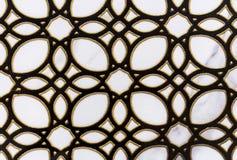 L'ornamento openwork nero con un oro rasenta una piastrella di ceramica bianca fotografia stock