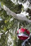 L'ornement de Noël sur la neige a couvert le pin Images stock