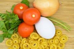 L'oro crudo fresco ha colorato la pasta, i pomodori, l'uovo, il prezzemolo e la cipolla fotografia stock libera da diritti