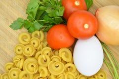 L'oro crudo fresco ha colorato la pasta, i pomodori, l'uovo, il prezzemolo e la cipolla immagini stock libere da diritti