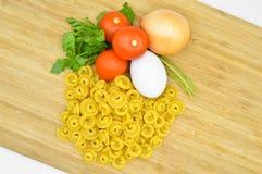 L'oro crudo fresco ha colorato la pasta, i pomodori, l'uovo, il prezzemolo e la cipolla immagini stock