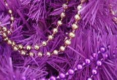 L'oro e le ghirlande porpora della perla messi insieme su un magenta artificiale hanno colorato l'albero Immagini Stock Libere da Diritti