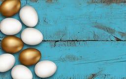 L'oro e le uova di Pasqua bianche sul blu hanno spazzolato il fondo di legno Uova di Pasqua dorate variopinte su una tavola di le fotografia stock libera da diritti