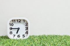 L'orologio bianco del primo piano per decora la manifestazione un il quarto a sette o 6:45 a M. sul pavimento verde dell'erba e s Fotografia Stock Libera da Diritti