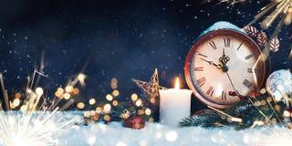 L'orologio del nuovo anno con la decorazione su neve immagini stock libere da diritti