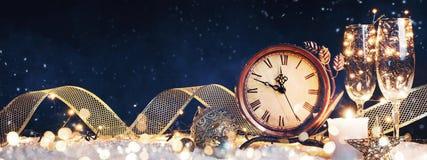 L'orologio del nuovo anno con le decorazioni di natale su neve immagine stock