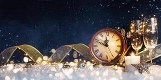 L'orologio del nuovo anno con le decorazioni di natale su neve fotografia stock