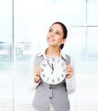 L'orologio della tenuta di sorriso della donna di affari pensa cerca Fotografia Stock