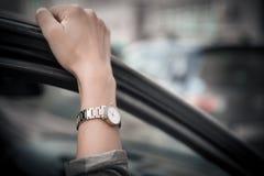 L'orologio delle donne sulla mano della ragazza Ragazza in fretta, stando in un ingorgo stradale Il tempo ? denaro L'uomo perde i fotografie stock