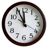 L'orologio di parete mostra mezzogiorno di mezzanotte, bianco isolato immagini stock