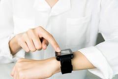 L'orologio digitale del touch screen della donna nell'esposizione e nella tecnologia avanza nella comunicazione Ciò è una nuova t fotografia stock