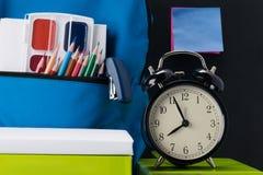 L'orologio indica che il suo tempo di andare a scuola e cose della scuola sulla tavola fotografia stock