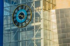L'orologio rotondo con i numeri romani ed il rame hanno colorato le mani Fotografia Stock Libera da Diritti