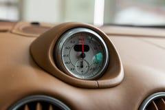 L'orologio sul cruscotto di un'automobile costosa è primo piano, coperto di cuoio beige naturale, con un quadrante bianco, una fr immagini stock