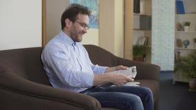L'oroscopo allegro della lettura dell'uomo in giornale e nella vita godere, weekend a casa stock footage