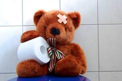L'orsacchiotto del giocattolo riguarda la toletta del wc immagine stock libera da diritti