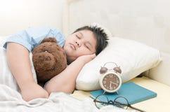 L'orsacchiotto grasso di sonno e dell'abbraccio del ragazzo riguarda il letto Fotografia Stock