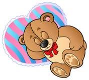 L'orsacchiotto riguarda il cuscino a forma di cuore Fotografia Stock