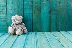 L'orsacchiotto riguarda il fondo di legno del turchese Fotografia Stock Libera da Diritti