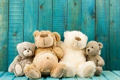 L'orsacchiotto riguarda il fondo di legno del turchese Immagini Stock Libere da Diritti