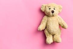 L'orsacchiotto riguarda il fondo rosa Immagine Stock