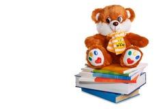 L'orsacchiotto riguarda il mucchio dei libri Fotografia Stock Libera da Diritti