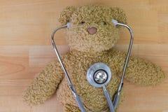 L'orsacchiotto riguarda il pavimento di legno con lo stetoscopio con i ricevitori telefonici nell'ea Immagini Stock