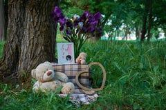 L'orsacchiotto riguarda l'erba con i fiori immagini stock