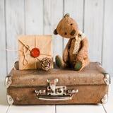 L'orsacchiotto riguarda una valigia con i messaggi di amore Immagini Stock Libere da Diritti