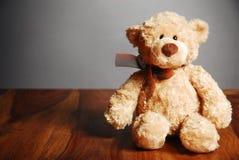 L'orsacchiotto sveglio riguarda una tabella Fotografie Stock Libere da Diritti