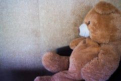 L'orso della bambola che aspetta sul sofà nero Fotografia Stock