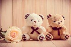 L'orso delle coppie si siede vicino alla rosa del pastello, fondo di legno fotografia stock libera da diritti