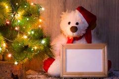 L'orso di Natale, del nuovo anno che si siede sotto un albero di abete con i modelli di una struttura di legno per una foto o tes fotografia stock