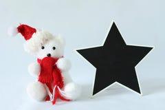 L'orso polare che portano un cappello e una sciarpa rossa per la decorazione della festa di Natale con un messaggio vuoto slate Immagine Stock