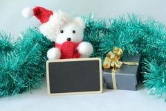 L'orso polare che portano un cappello e una sciarpa rossa per la decorazione della festa di Natale con un messaggio vuoto slate Immagini Stock