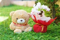 L'orso si siede sull'erba vicino al fiore fotografia stock