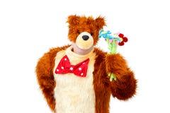 L'orso strano con il giocattolo fiorisce su fondo bianco Fotografia Stock