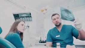 L'orthodontiste dit le patient au sujet des dents de sagesse banque de vidéos
