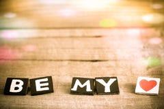 L'orthographe en bois de lettres soit mon amour avec Bokeh coloré sur en bois Image stock