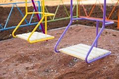 L'oscillation des enfants sur le terrain de jeu dans la cour photos stock