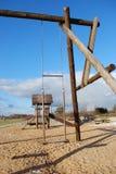 L'oscillazione di legno dei bambini in un parco pubblico di ricreazione Fotografie Stock