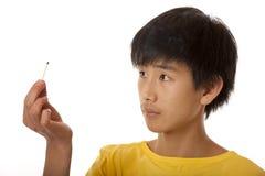 L'osservazione asiatica del ragazzo brucia la corrispondenza Fotografie Stock Libere da Diritti