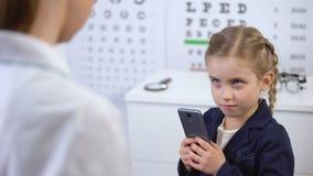 L'ottico che prova a prendere il cellulare dal bambino impertinente, video giochi danneggia la vista archivi video