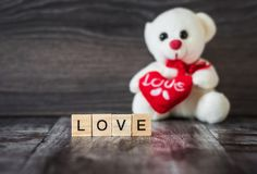 L'ours blanc de jouet mou tenant un coeur et le mot aiment, esprit rayé Photos stock