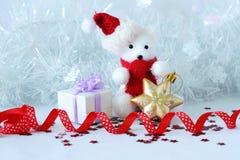 L'ours blanc utilisant un chapeau et une écharpe bleue a posé à côté des cadeaux avec les noeuds brillants sur un décor de vacanc Images stock