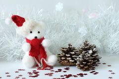 L'ours blanc utilisant un chapeau et une écharpe rouge a posé à côté des cadeaux avec les noeuds brillants sur un décor de vacanc Photos stock